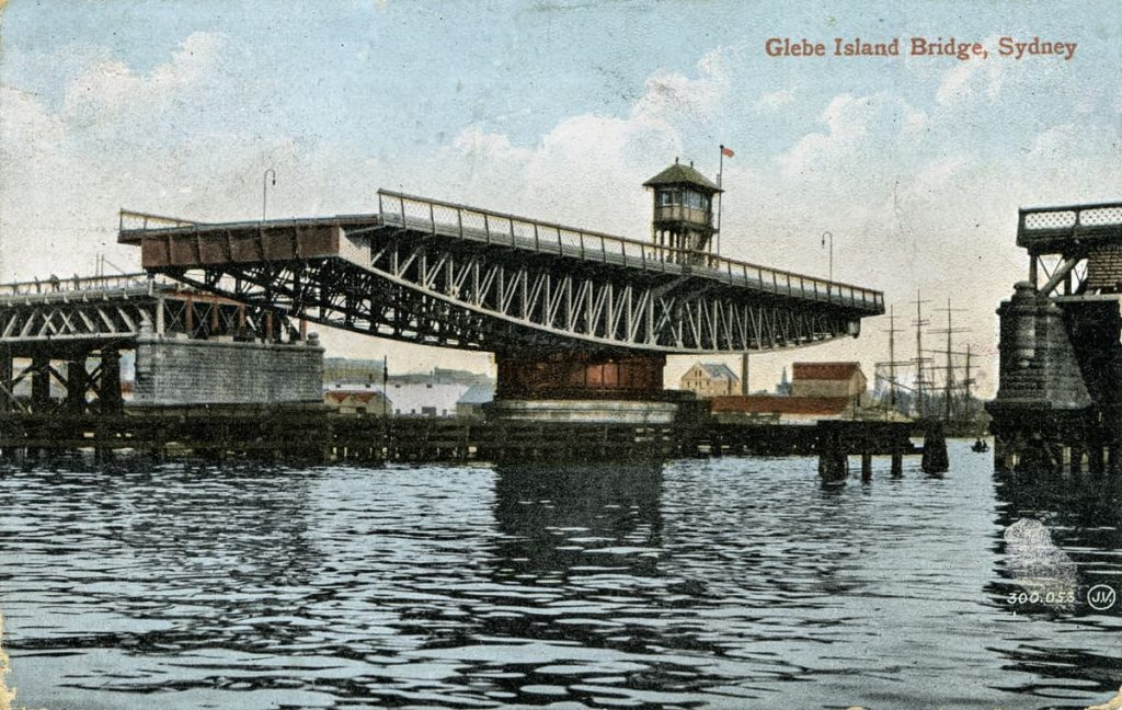 """Coloured postcard view of thebridge, swung open to allow shipping to pass through. On reverse personal message about weather and sightseeing, """"like Sydney very much"""". 1915. Image courtesy of City of Sydney Archives"""
