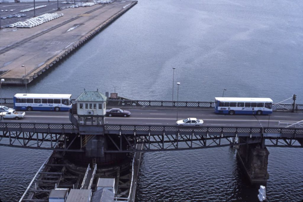 State Transit Mercedes 0405 MK V 3152 and 3150 cross the oldGlebeIslandBridgejust a day before the opening of the new AnzacBridgebuilt alongside. The buses are heading towards Bank Street, Pyrmont and ultimately the City. 2nd December 1995. Photographer: John Ward. Image courtesy of City of Sydney Archives